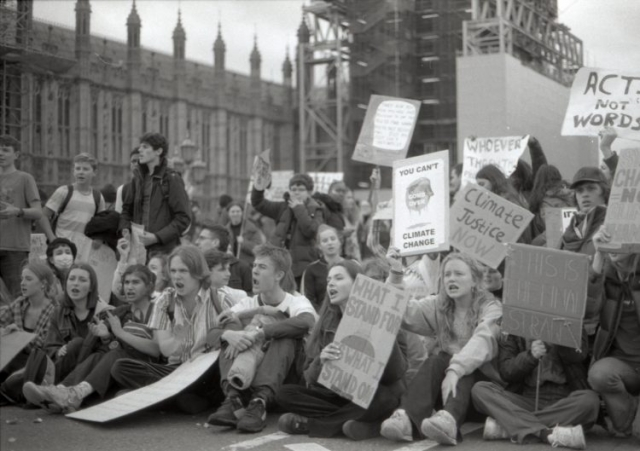 a croud of youngsters sitting in protest with banners