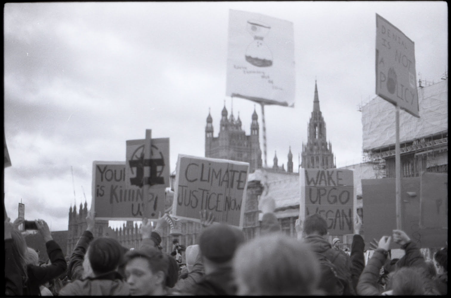 a crowd holding up banners in front of the parliament skyline