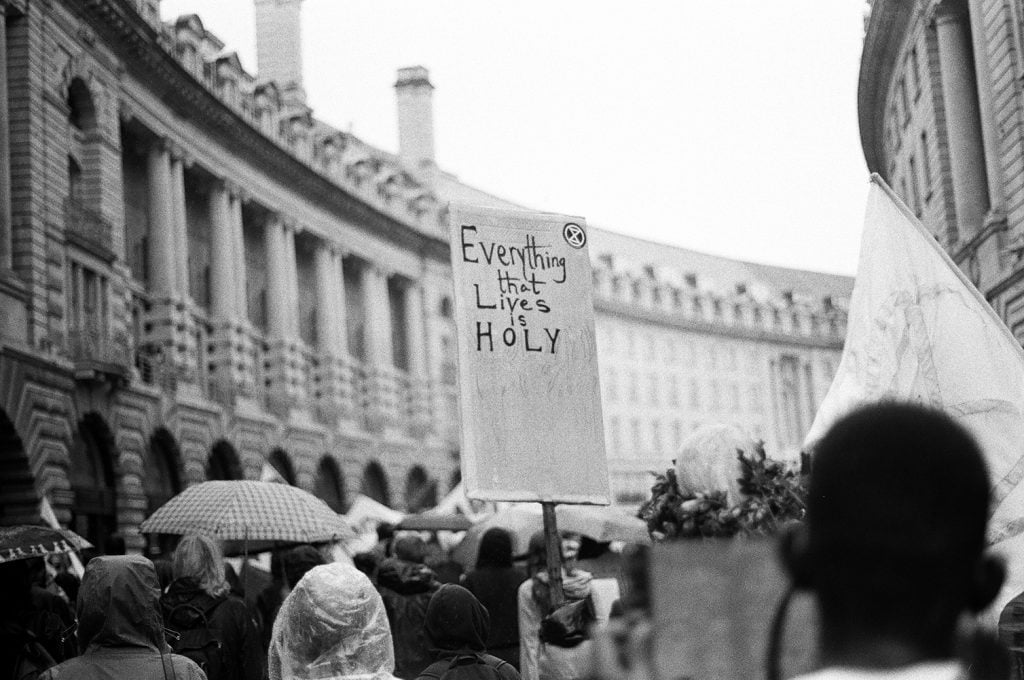 a photo at the SCHOOL STRIKE FOR CLIMATE of a banner reading 'Everything that lives is Holy.'